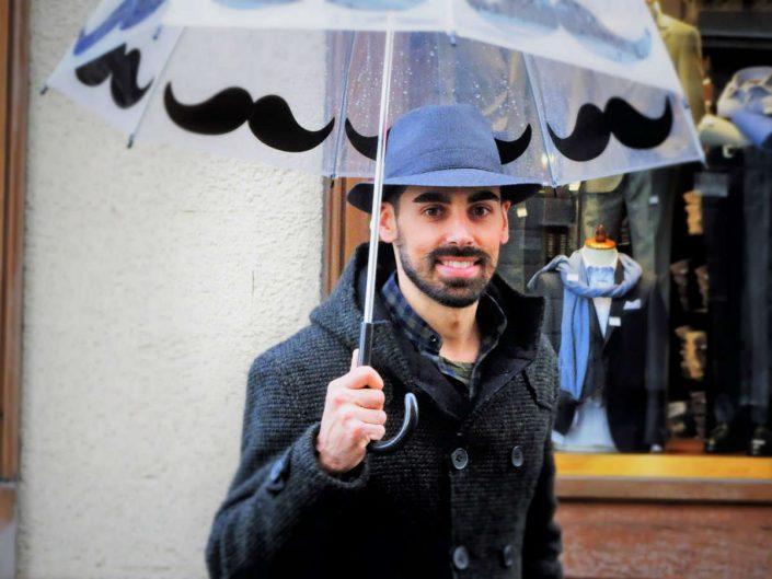 Un ragazzo indossa un cappello invernale sotto ad un ombrello