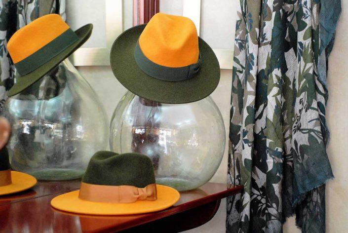 Due cappelli di due colori alternati, giallo senape e verde bosco, da uomo, appoggiati su una mensola
