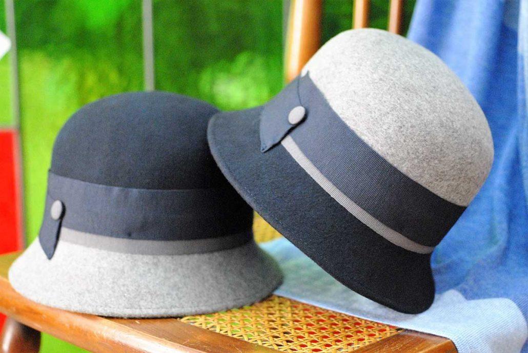 Due piccole cloche in feltro blu e grigielu e grigio, appoggiate su una sedia