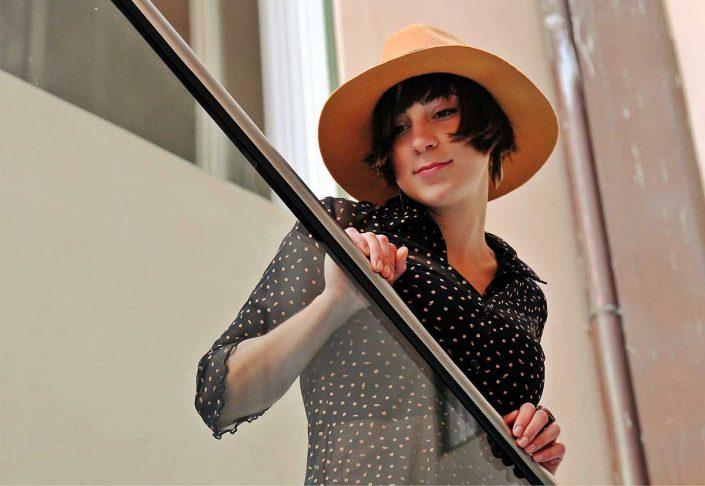 Una ragazza si affaccia da una balaustra di una scala, indossa un bel cappello in fletro di lepre giallo ocra.